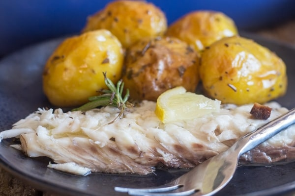 baked trout slice and potatoes on a black plate