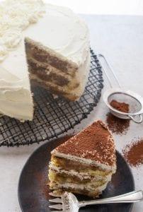 tiramisu layer cake with a slice cut and on a plate