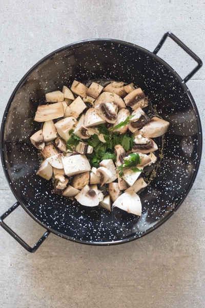cooking the mushrooms in a black pan