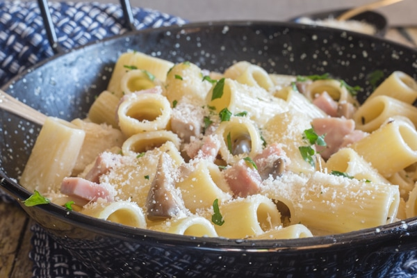 mushroom and ham pasta sprinkled with parmesan cheese in a black pan