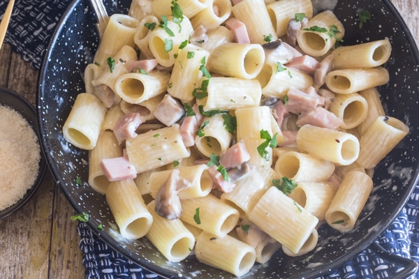 up close mushroom & ham pasta in a black pan