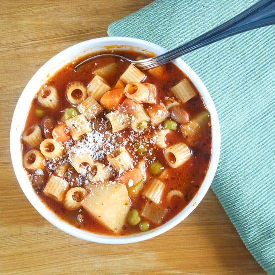 a bowl of minestrone soup with a silver spoon