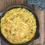 asparagus frittata in a skillet on a wooden board