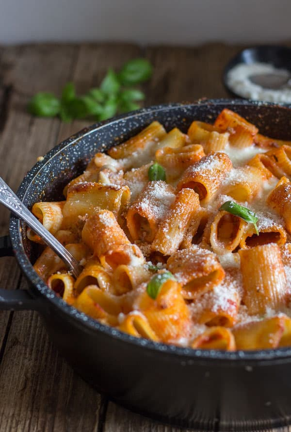 a skillet of baked pasta with a spoon in it and sprinkled with parmesan cheese
