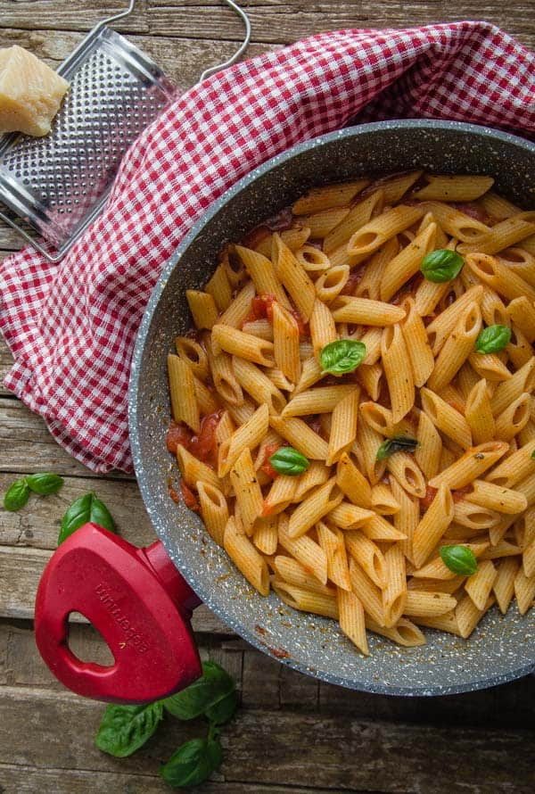 a pan with cooked pasta & easy tomato sauce topped with fresh basil leaves