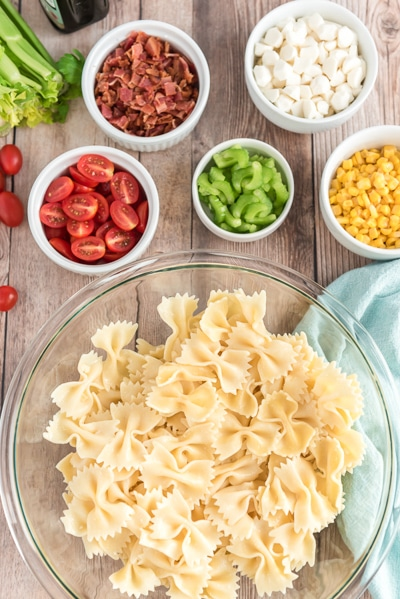 ingredients to make salad, pasta, tomatoes, celery, corn, pancetta & corn in bowls