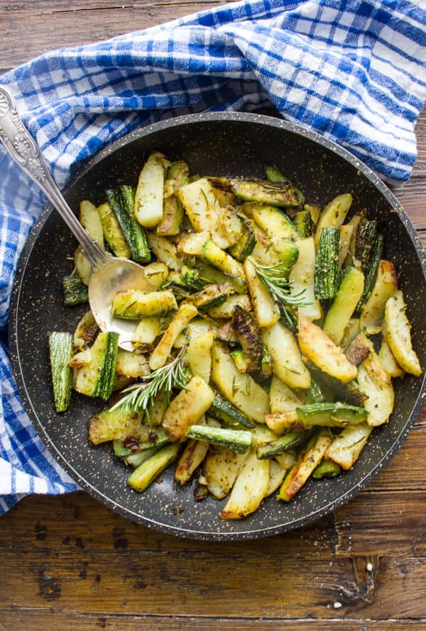 roasted zucchini & potatoes in a black pan with a silver serving spoon and a blue and white napkin