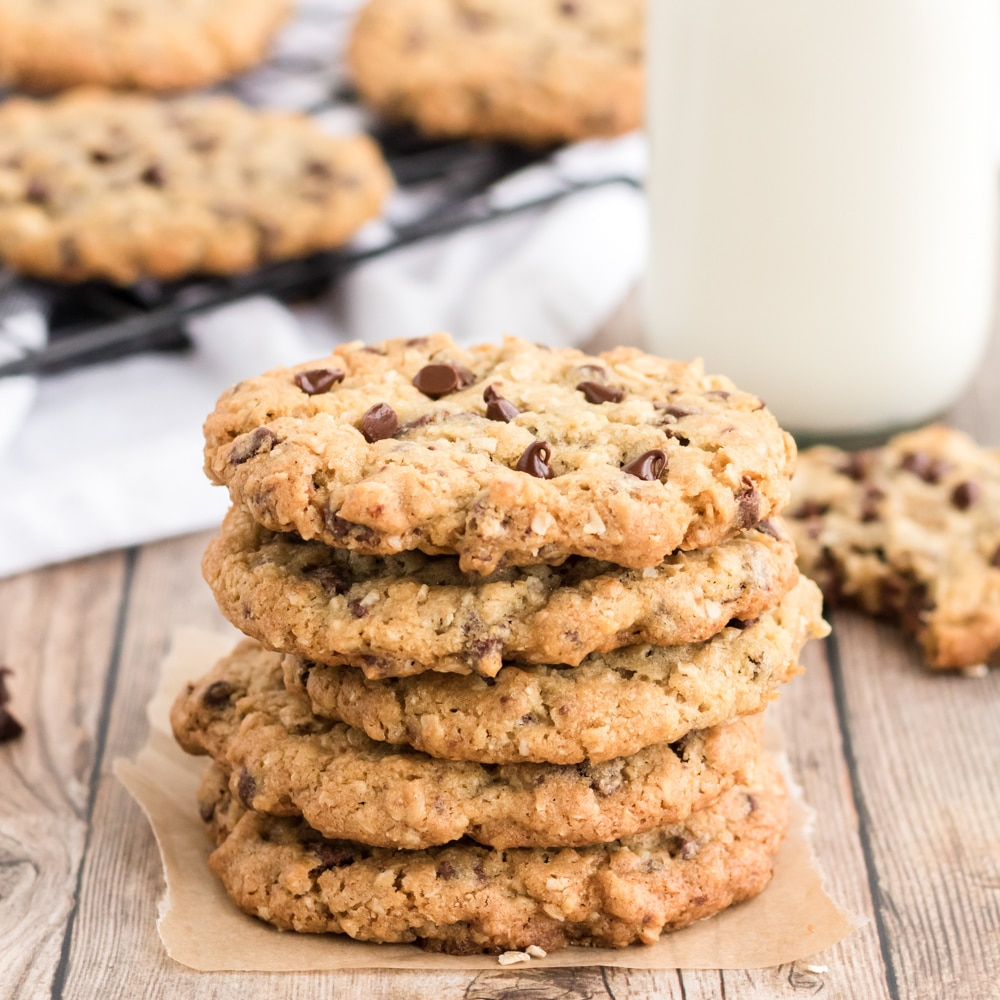 oatmeal chocolate chip cookies stacked on a wooden with a bottle of milk