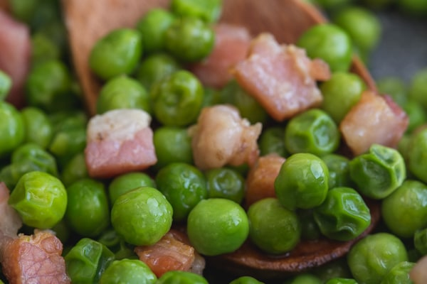 up close peas on a wooden spoon