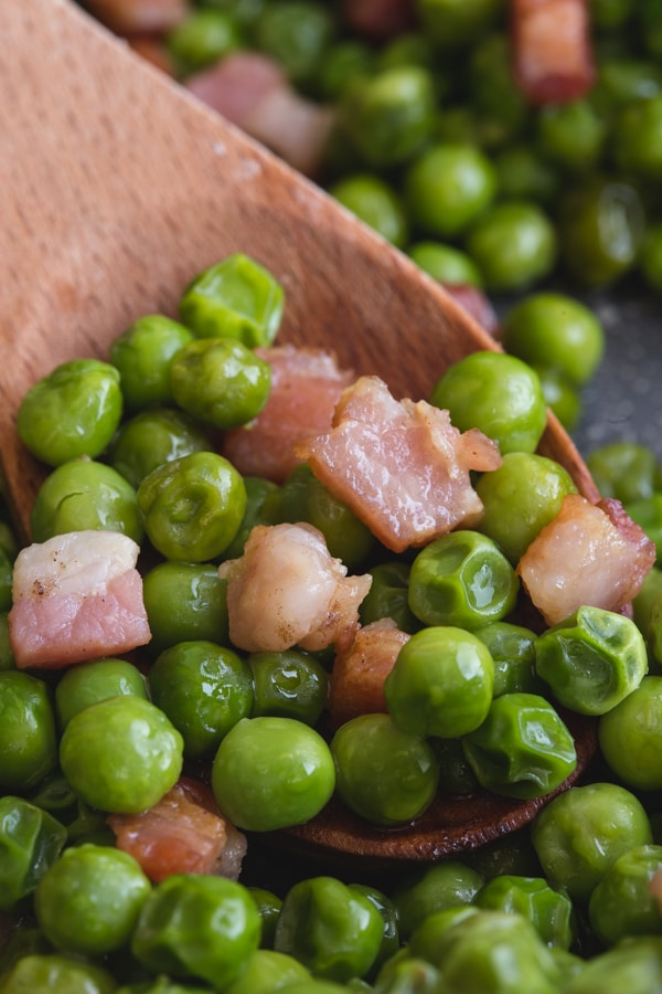 peas and pancetta on a wooden spoon