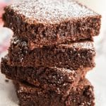 4 brownies stacked sprinkled with powdered sugar