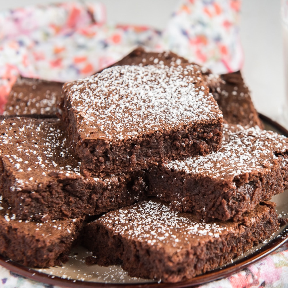 brownies cut and stacked on a plate dusted with powdered sugar