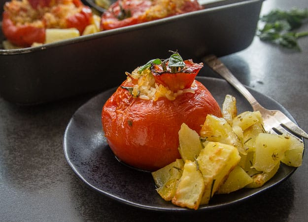 stuffed tomatoes with rice and roasted potatoes on a plate