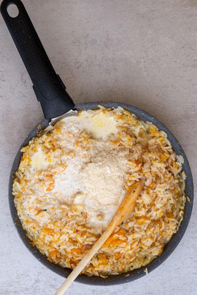 Adding the parmesan cheese and butter to the rice.