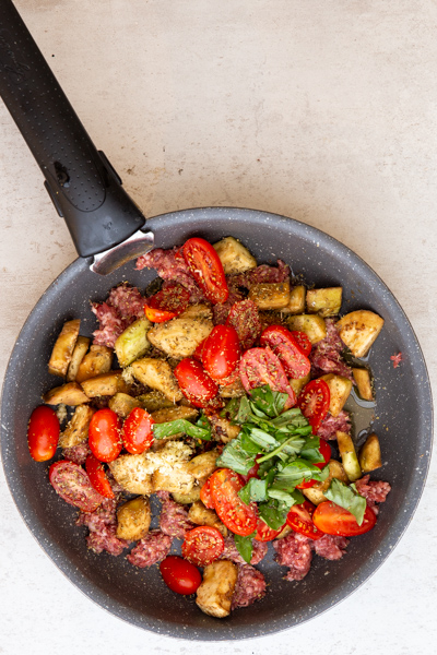 veggies and spices in a black pan