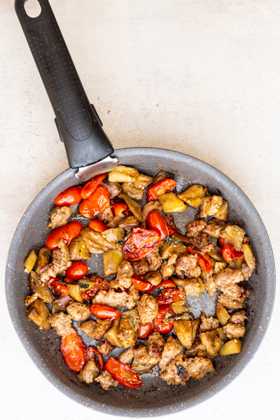 cooked veggies and spices in a black pan