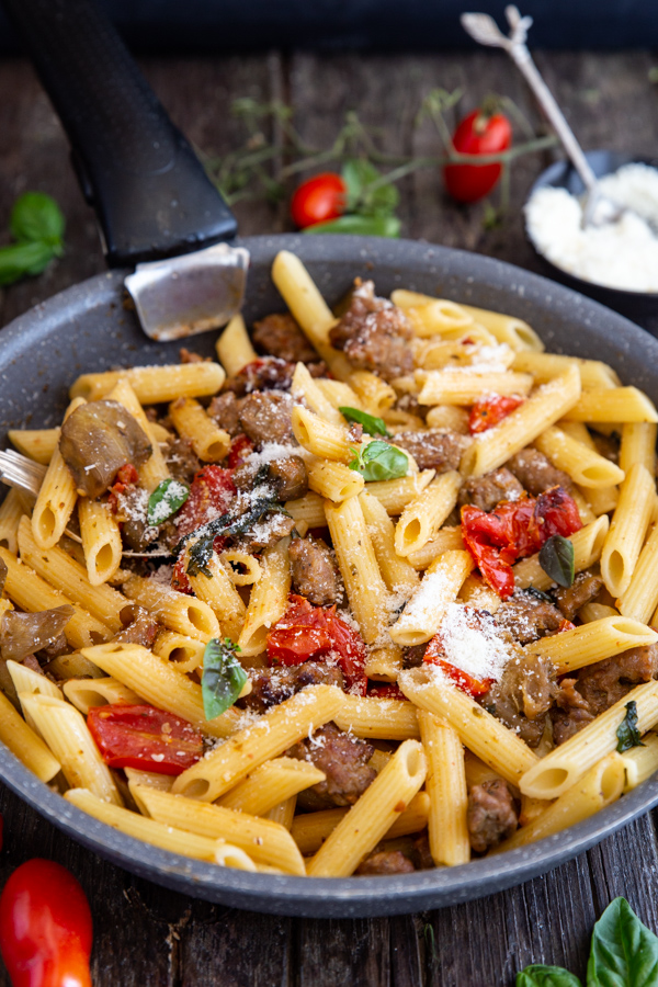 sausage pasta in a black pan with sprinkled parmesan cheese on top