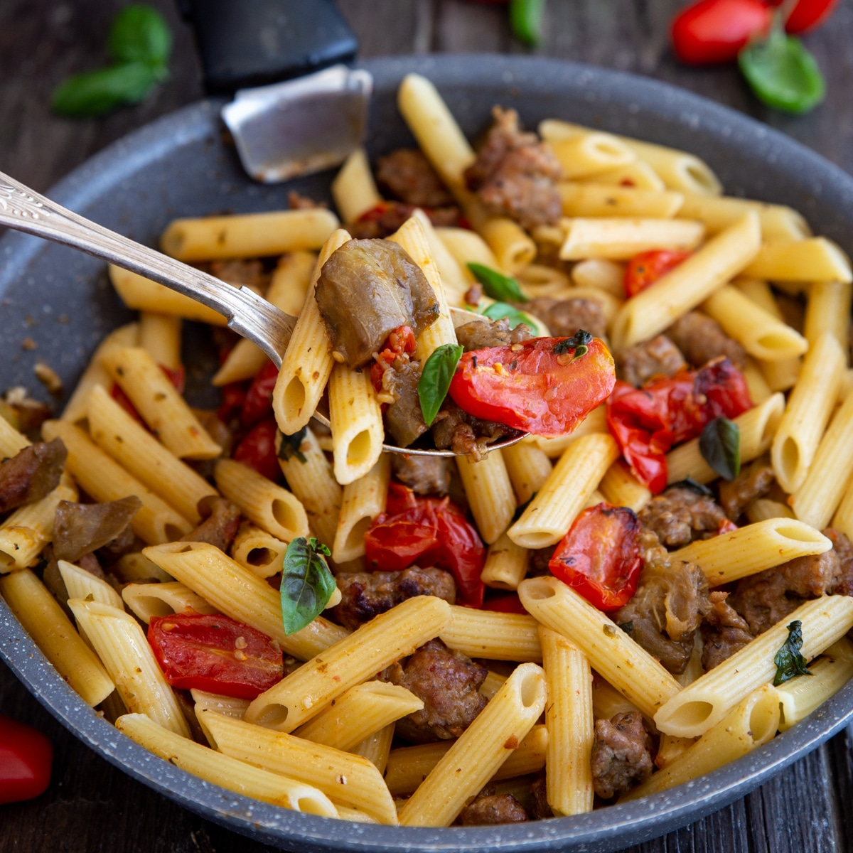 sausage pasta in a black pan with some on a silver spoon