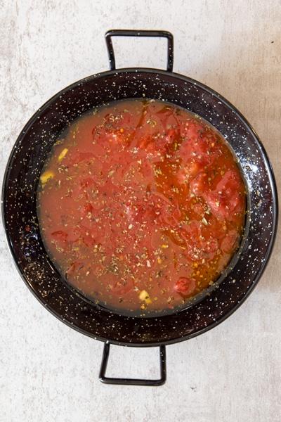 adding the sauce to the black pan to make tuna olive pasta