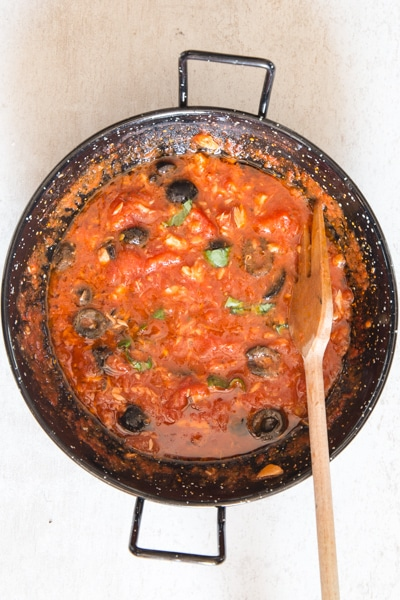 tuna and olive pasta sauce is ready in a black pan
