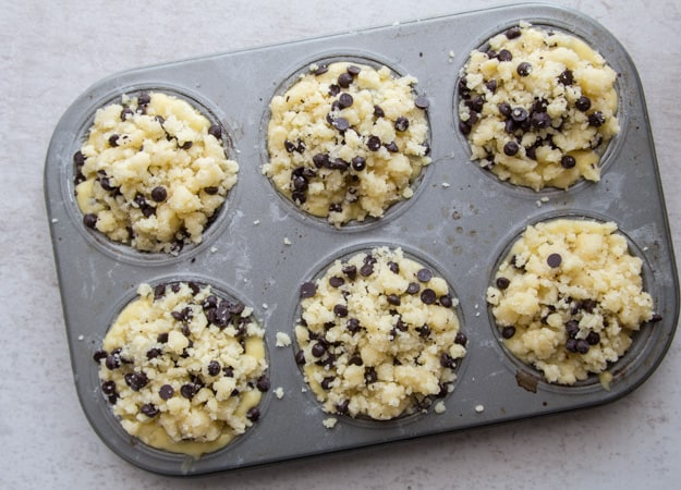 a muffin tin with muffin mix before baked