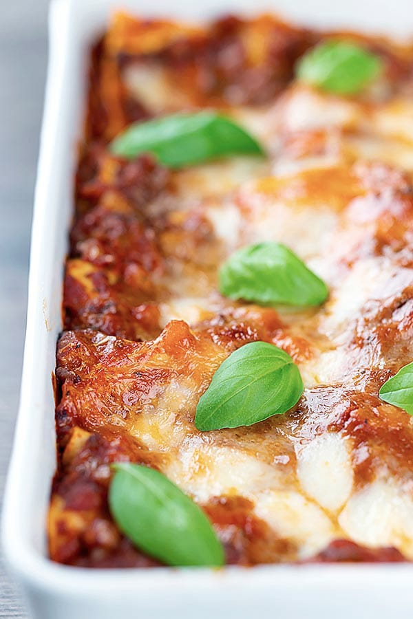 lasagna in a white pan with basil leaves on top