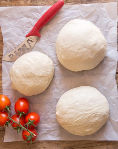 pizza dough 3 rounds on parchment paper
