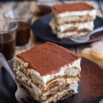 2 slices of tiramisu on black plates