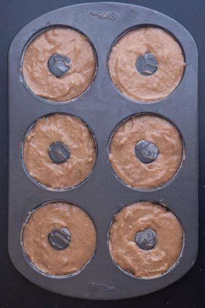 बेकिंग से पहले डोनट पैन में डोनट बटर।