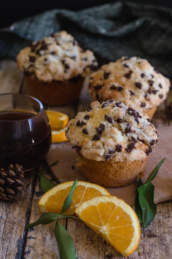 3 orange muffins on a wooden board