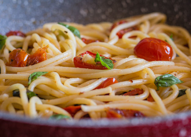 a pan of spaghetti with oven dried parmesan tomatoes