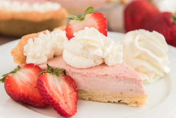 a slice of pie with whipped cream and strawberry slice