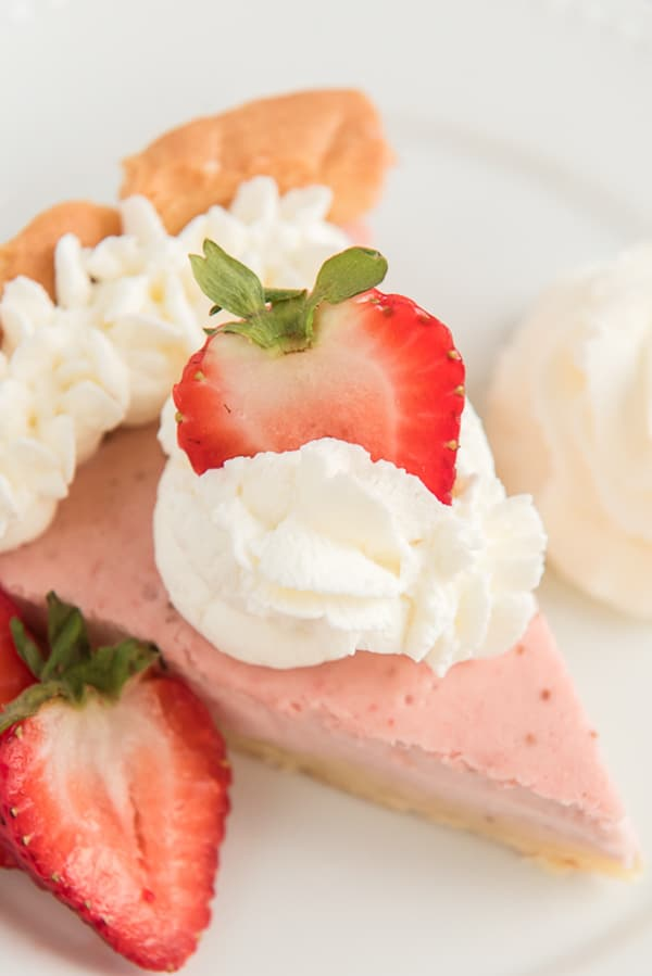 a slice of pie on a white plate with whipped cream and a slice of strawberry on top
