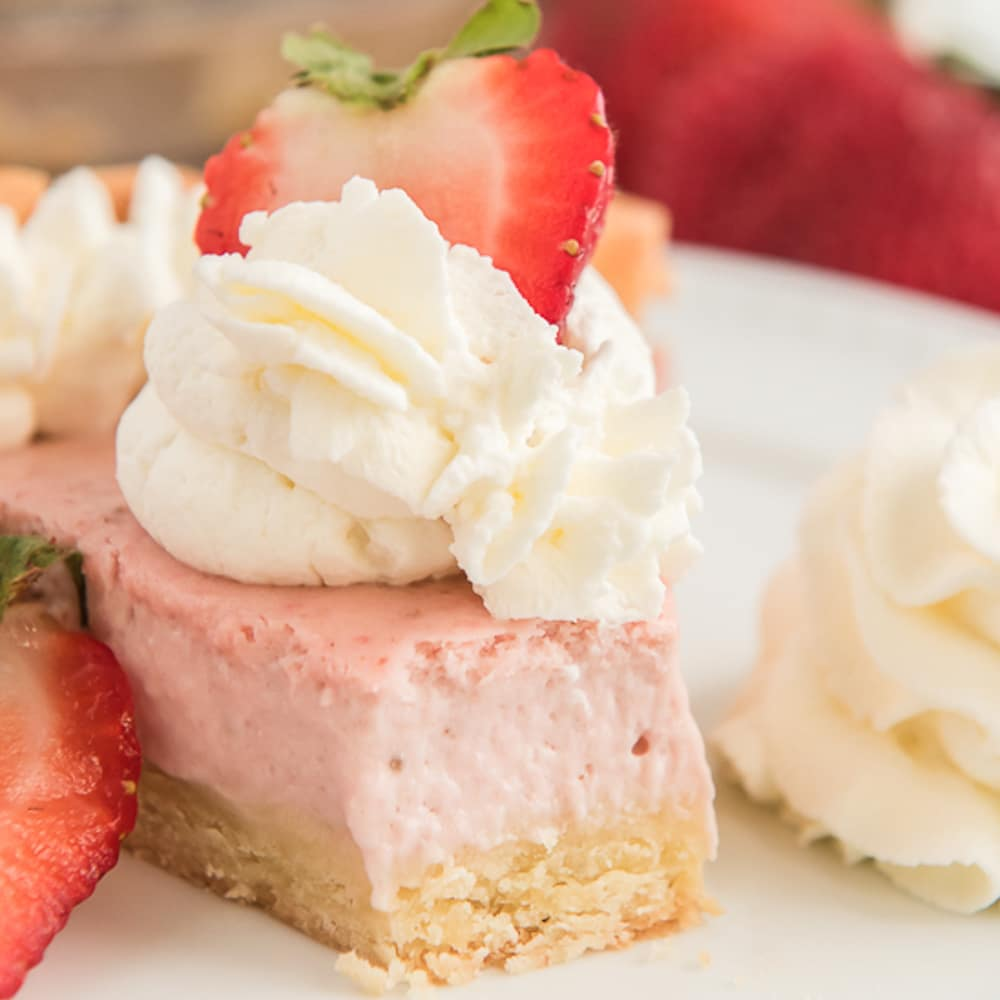 sliced pie with a forkful removed topped with whipped cream and a strawberry slice