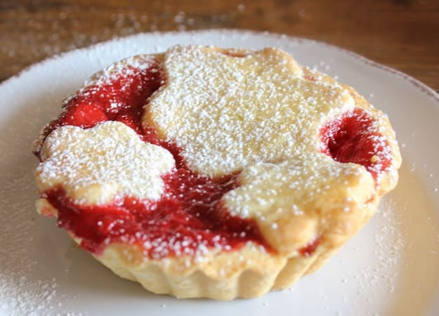 a strawberry filled tart baked and sprinkled with sugar on a white plate