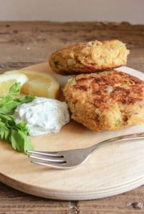salmon burgers on a wooden plate with yogurt dill sauce