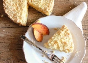 a slice of peach crumb cake on a white plate with 2 slices of peaches