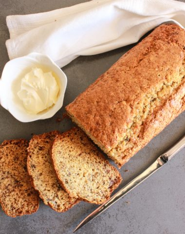 banana bread with 3 slices, a knife and butter in a white dish