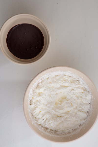 melted chocolate in a white bowl and the whipped cream in a white bowl