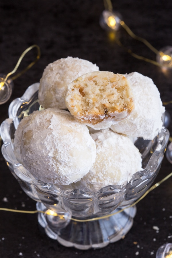 a broken snowball cookie with whole cookies in a glass bowl