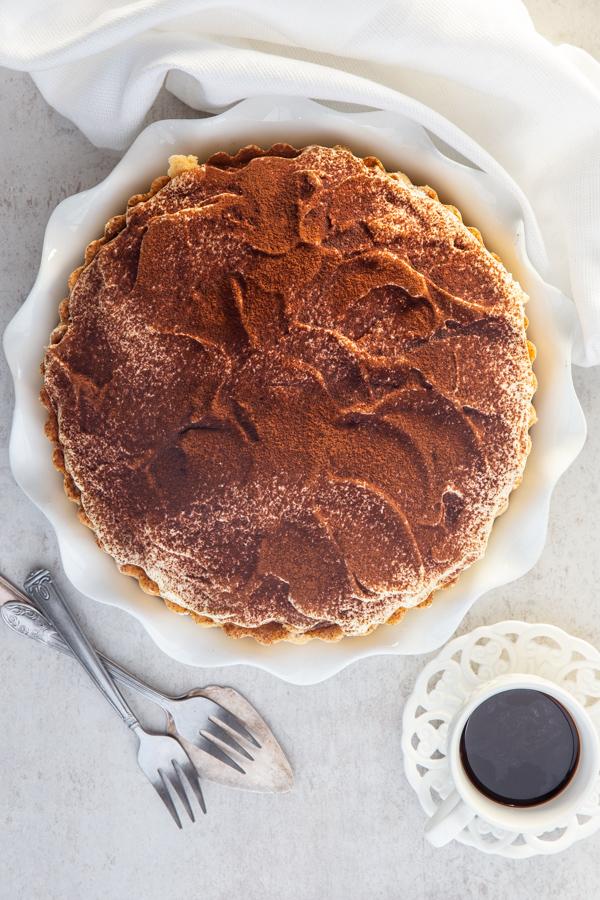 tiramisu pie in a white pie plate with an espresso