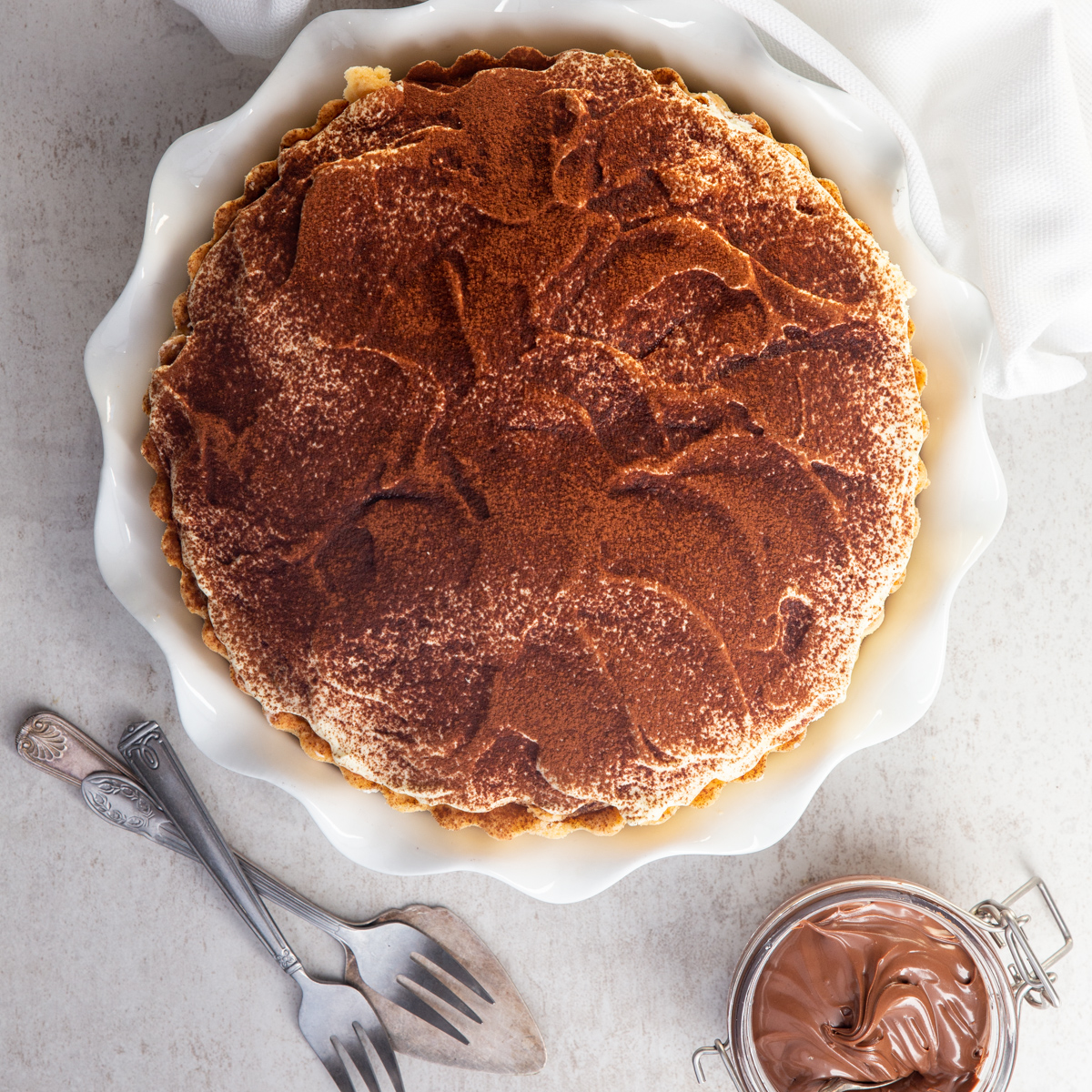 tiramisu pie on a white board in a white pie plate with a jar of hazelnut cream