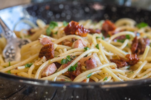 cooked pasta with sun-dried tomatoes in a black pan