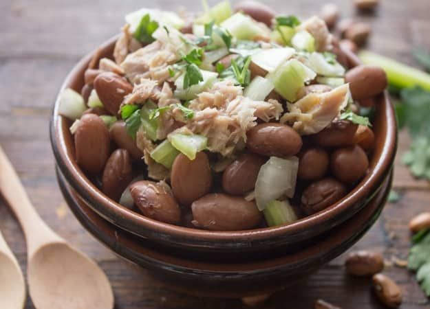 bean salad with chopped parsley on top in a brown bowl with wooden spoons