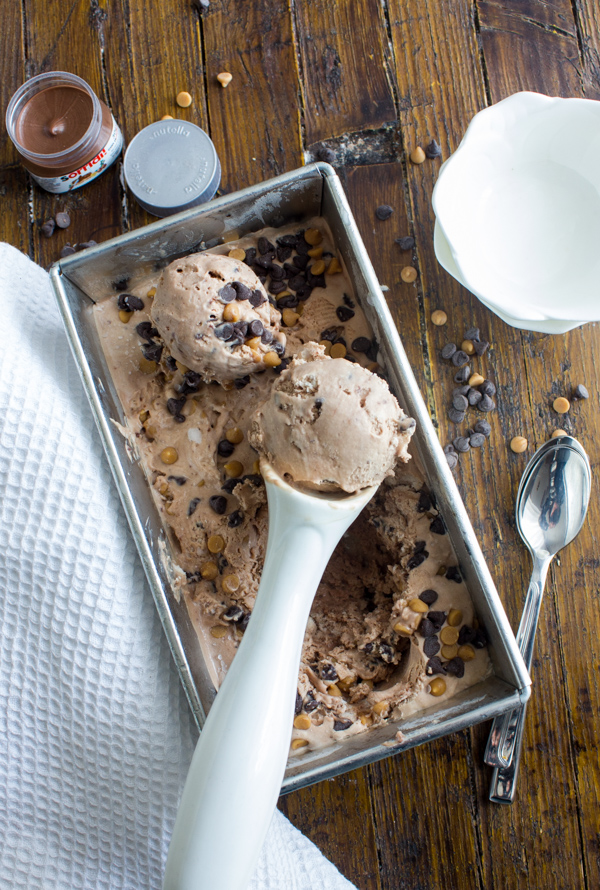 Nutella Peanut Butter Chocolate Chip Ice Cream, 2 scoops sitting on the ice cream in the loaf pan on a wooden board, a small white bowl and spoon.