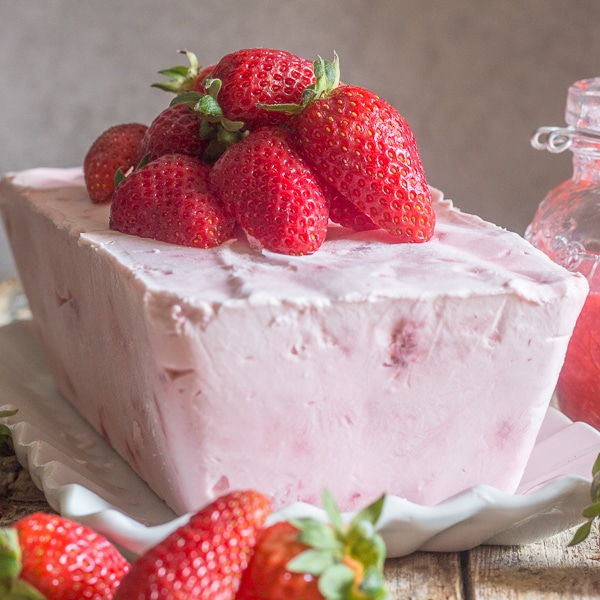 semifreddo on a plate topped with fresh strawberries