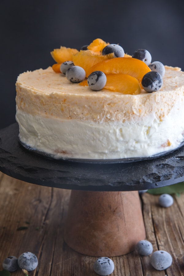 apricot cake on a black cake stand