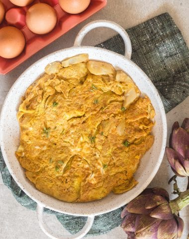 frittata in a white baking dish with eggs in a dish and an artichoke
