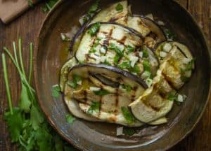 grilled eggplant in a bowl with garlic, parsley and olive oil