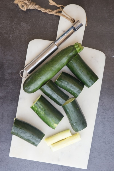 removing the pulp from the zucchini on a white board